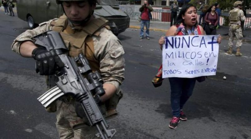 "A woman holds a sign saying ""No soldiers on the streets"". Phot: Chile Solidarity Network/Twitter"